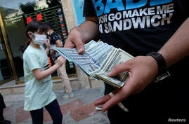 An unauthorised seller counts U.S. dollars in front of an Exchange shop at Ferdowsi square in Tehran