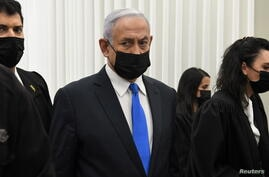 Israeli Prime Minister Benjamin Netanyahu wears a protective face mask as he stands inside the courtroom just before the start of a hearing in his corruption trial at Jerusalem's District Court
