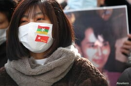 A protester wears a face mask with the Myanmar flag and National League for Democracy flag as they rally against Myanmar's military after it seized power from a democratically elected civilian government and arrested its leader Aung San Suu Kyi, in Tokyo