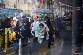 FILE PHOTO: An Iranian woman carries a picture of Iran's Supreme Leader Ayatollah Ali Khamenei during a ceremony to mark the 40th anniversary of the Islamic Revolution in Tehran