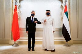 China's State Councilor and Foreign Minister Wang Yi and UAE's Foreign Minister Abdullah Bin Zayed Al Nahyan do an elbow shake during their meeting in Abu Dhabi