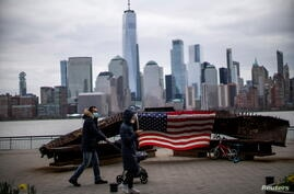People wear face mask as they walk near a 9-11 memorial during the coronavirus disease (COVID-19) pandemic, while the One World Trade Center and New York skyline are seen from Exchange Place, in New Jersey