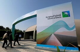 FILE PHOTO: Logo of Aramco is seen as security personnel walk before the start of a press conference by Aramco at the Plaza Conference Center in Dhahran