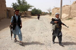 Armed Afghan militias patrol on the outskirts of Takhar province