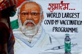 FILE PHOTO: A woman walks past a painting of Indian Prime Minister Narendra Modi in Mumbai a day before inauguration of India's COVID-19 vaccination drive