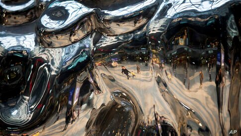 Shoppers are reflected on an art installation on display at a shopping mall in Beijing, China, Dec. 7, 2013.