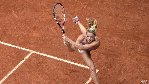 Italy's Camila Giorgi returns the ball to Russia's Svetlana Kuznetsova during the French tennis Open second round match at the Roland Garros stadium in Paris, France.