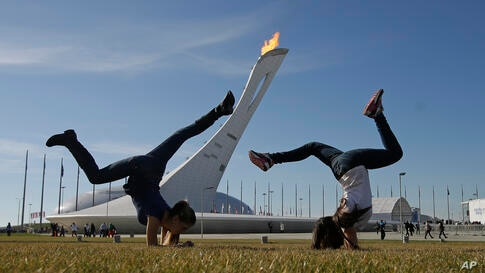 Young girls play on a warm day in the Olympic Plaza, Sochi, Russia, Feb. 12, 2014.