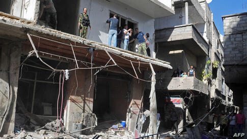Syrian citizens and security forces inspecting the sight of a car bomb attack in Damascus' Tadamun neighborhood.