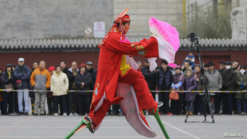 A folk artist on stilts performs at a temple fair celebrating the traditional Chinese Spring Festival on the second day of the Chinese Lunar New Year at Dongyue Temple, in Beijing.