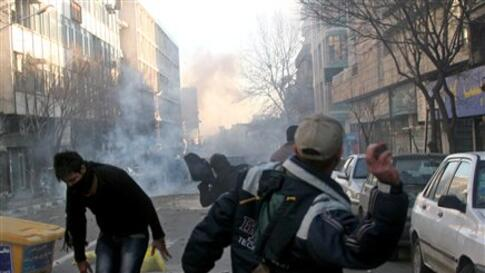This photo, taken by an individual not employed by the Associated Press and obtained by the AP outside Iran shows Iranian protestors throwing stones at ant-riot police officers, during an anti-government protest in Tehran, Iran, Monday, Feb. 14, 2011. Eye