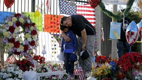 Gary Mendoza, and his son Michael pay their respects at a makeshift memorial site honoring shooting victims in San Bernardino, California. Thousands of employees of San Bernardino County are preparing to return to work, five days after a county restaur...
