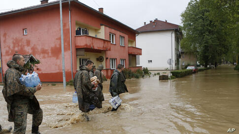 Members of the army carry food and water supplies for people stranded, due to the floods, in the Bosnian town of Maglaj, May 16, 2014.