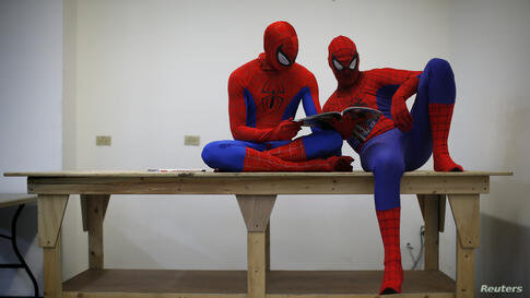 """Peter Norbot and Kris Hamilton (L), dressed up as fictional comic book superhero Spider-Man, look through a magazine as they wait for their turn to audition to be a part of a promotional campaign for the upcoming release of the new movie """"The Amazing S..."""