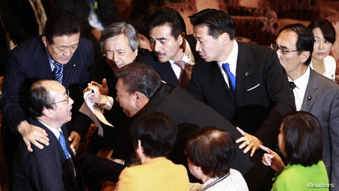 Masaharu Nakagawa (bottom, L), chairman of the Upper House Special Committee on National Security, is surrounded by lawmakers during a vote on a state secrets act at the parliament in Tokyo, Japan.