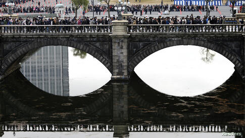 Well-wishers cross a bridge outside the Imperial Palace as they make their way to attend an event to celebrate Japan's Emperor Akihito's 80th birthday at the Imperial Palace in Tokyo.