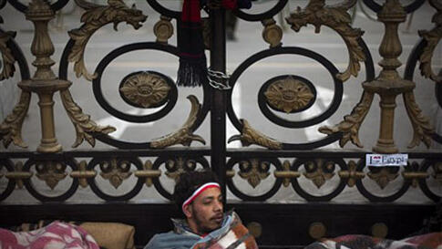 An anti-government protester wakes up after spending the night in front of the main gate of the Egyptian Parliament in Cairo, February 10, 2011