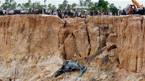 Soldiers use a crane to lift an aft section of a helicopter retrieved from a pond following its crash in Prey Sar village at the outskirt of Phnom Penh, Cambodia.