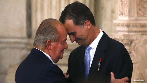 Spain's King Juan Carlos and his son Crown Prince Felipe (R) hug each other as they attend the signature ceremony of the act of abdication at the Royal Palace in Madrid.