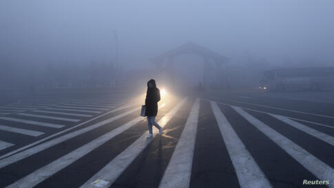 A woman walks along a street during a smoggy day in Changchun, Jilin province. The severe smog continued to shroud major cities in north-east China including Changchun.