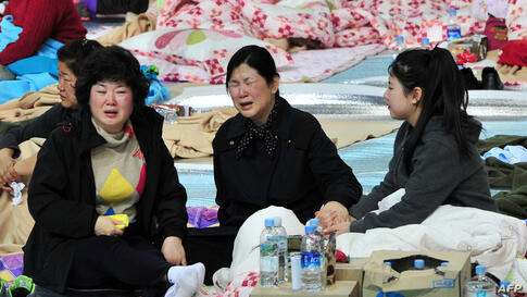 South Korean relatives of passengers on board a capsized ferry react as they wait for news at a gym in Jindo.
