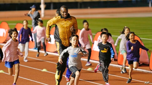 "Olympic gold medalist Usain Bolt of Jamaica ""competes"" with children during an athletic clinic at the national stadium in Tokyo, Japan."