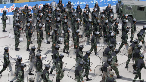 Soldiers hold their shields as they prepare to leave after guarding a shopping district to stop protests against military rule in central Bangkok, Thailand.