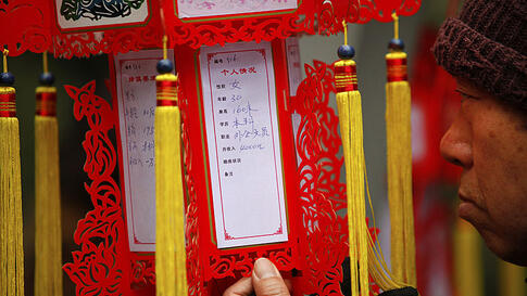 A parent looks at a red lantern with personal information displayed during a Valentine's Day event at the People's Park in Shanghai, February 14, 2012. The event is organized by the local government to help parents look for dating opportunities for their