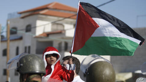 A Palestinian child dressed as Santa Claus holds a Palestinian flag while standing in front of Israeli border police during a demonstration against Israel's separation barrier in the West Bank village of Al-Masara, near Bethlehem.