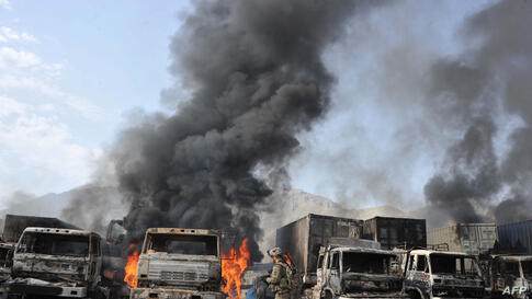 A U.S. soldier walks past burning trucks at the scene of a suicide attack at the Afghan-Pakistan border crossing in Torkham, Nangarhar province.