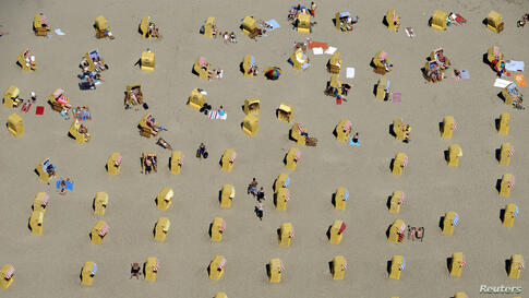 People take a sunbath in beach chairs at a beach in Travemuende by the Baltic Sea, Germany.