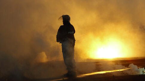 A policeman stands amidst thick smoke from flares during a Europa League Group soccer match between CSKA Sofia and Besiktas in Sofia December 2, 2010. (Oleg Popov/Reuters)