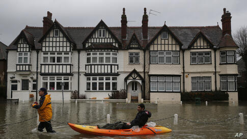 A man sits in a boat pulled by another man through a flooded street, in the center of the village of Datchet, England. The River Thames has burst its banks after reaching its highest level in years, flooding riverside towns upstream of London.