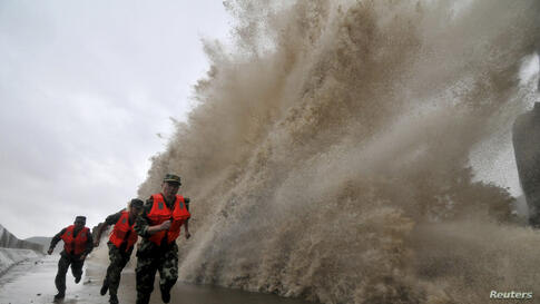 Frontier soldiers run as a storm surge hits the coastline under the influence of Typhoon Fitow in Wenling, Zhejiang province, China, Oct. 6, 2013.