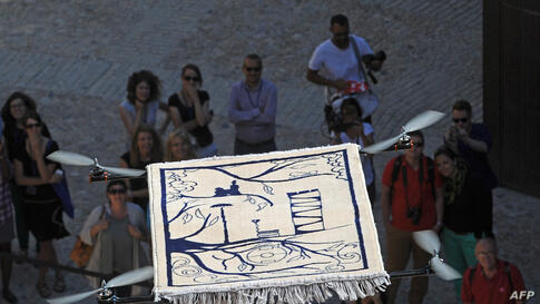 """People watch the """"Flying Carpet"""", an artwork created by French artist Moussa Sarr, as it takes off from the Saint Jean fort in Marseille, southern France. It's part of """"L'artiste dans la cite"""" ('The Artist in the City') events organized by the MUCEM, """"..."""