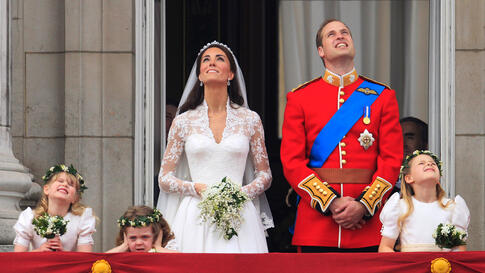 Prince William and his wife watch a fly-past of military planes from the balcony following the wedding. (AP Photo/Matt Dunham)