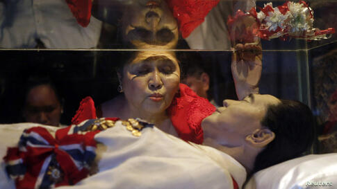 Former First Lady Imelda Marcos kisses the glass coffin of her husband, the late President Ferdinand Marcos, who remains unburied since his death in 1989, during her 85th birthday celebration in Ferdinand Marcos' hometown of Batac, Ilocos Norte provinc...