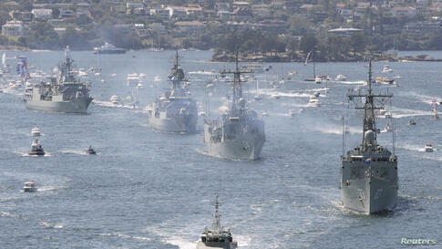 Royal Australian Navy warships led by HMAS Sydney (R) enter Sydney Harbor as part of the International Fleet Review celebrations. The Review marks the centenary of the first entrance into Sydney by the Royal Australian Navy's fleet, according to the Navy.