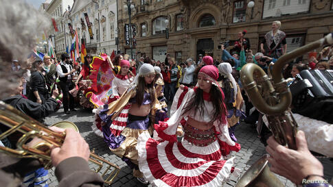 Participants of the Khamoro World Roma Festival dance through the historical center of Prague, Czech Republic. The festival aims to showcase Roma culture and improve relations between society and members of the Roma community.