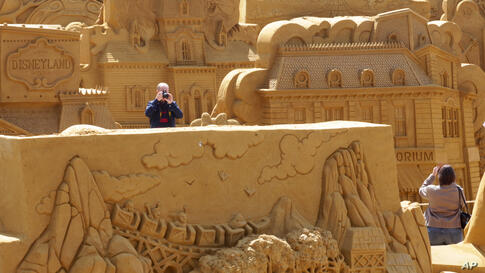 Visitors take photographs of sand sculptures on the beach at the Northsea town of Ostend, Belgium.