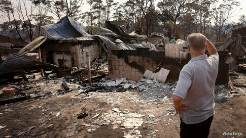 Local resident Colin Smith looks at the remains of his family's house after it was destroyed by a bushfire in the Blue Mountains suburb of Winmalee, located around 70 km west of Sydney, Australia.
