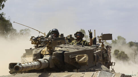 Israeli soldiers atop a tank outside the Gaza Strip, July 18, 2014.