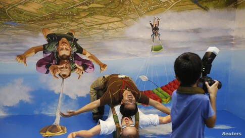 A visitor poses for photos with a 3-D installation at a media preview of the Trick Eye Museum at the Resorts World Sentosa in Singapore. The museum, which features paintings and optical illusion installations, will open to the public on Sunday.