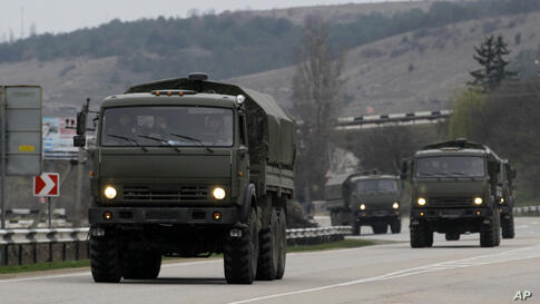 A convoy of hundreds of Russian troops headed toward the regional capital of Ukraine's Crimea region, a day after Russia's forces took over the strategic Black Sea peninsula without firing a shot. Pictured here, a Russian convoy moves from Sevastopol t...