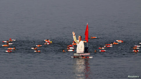 Participants swim together with a portrait of late Chinese Chairman Mao Zedong in the Hanjiang River, a large branch of the Yangtze River in Xiangyang, in Hubei province, July 13, 2014, to celebrate the upcoming 48th anniversary of Mao swimming in the ...
