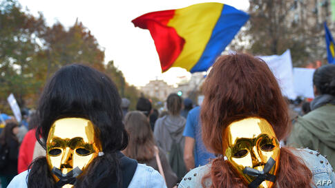 People wear golden masks during a protest in Bucharest, Romania. Thousands of people marched for the eighth week against a Canadian gold mine plan to extract 300 tons of gold and 1,600 tons of silver over 16 years, Oct. 20, 2013.