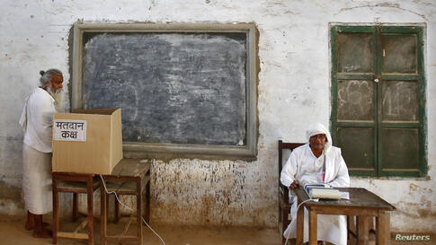 A sadhu (Hindu holy man) casts his vote at a polling station at Ayodhya in the northern Indian state of Uttar Pradesh.