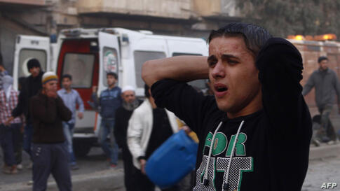A Syrian man reacts after an air strike by government forces on the city of Aleppo, Syria.