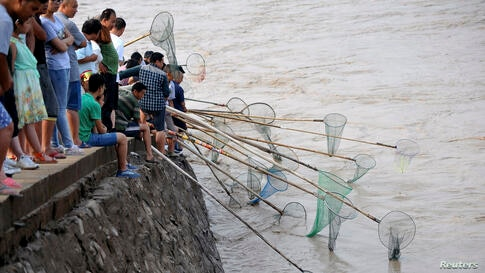 People fish along the bank of the Yellow River as the Sammenxia Dam discharges flood waters downstream in Pinglu, Shanxi province, China, July 6, 2014.