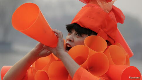 Chinese artist Kong Ning in her costume made of hundreds of orange plastic blowing horns during her art performance raising awareness of the hazardous smog in a historical part of Beijing, China.